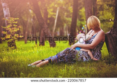 Young mother breast feeding young adorable baby in park.. The baby sucks a breast. The mother feeds the young baby in the countryside in the sunlight at sunset. Breast feeding. - stock photo