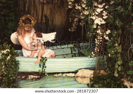 Young mother breastfeeding newborn baby dressed as angels with white wings in a boat on the river  - stock photo