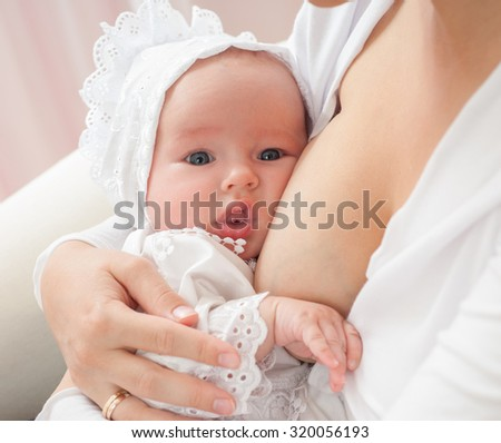 Young mother breastfeeds her baby. Breast-feeding.Happy family.Home interior. - stock photo