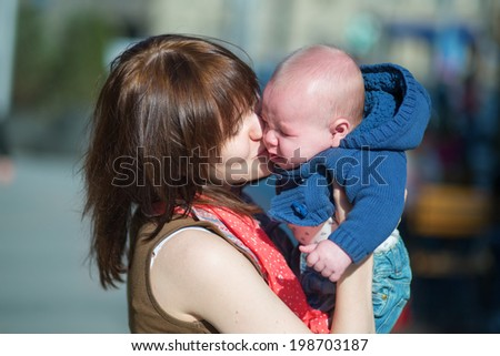 Young mother calming her crying baby boy - stock photo