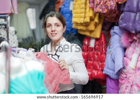 Young mother  chooses children's clothes at clothing store - stock photo