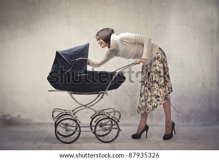 Young mother cuddling her baby lying in a pram - stock photo