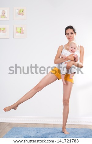 young mother does physical fitness exercises together with her baby - stock photo