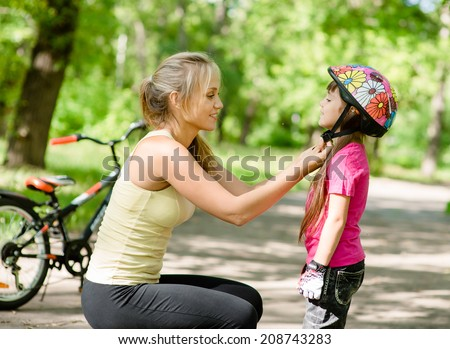young mother dresses her daughter's bicycle helmet - stock photo