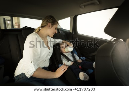 Young mother feeding baby boy with milk on car back seat - stock photo