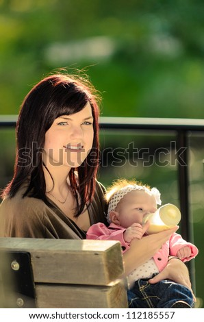 Young mother feeding baby in an outdoor park - stock photo