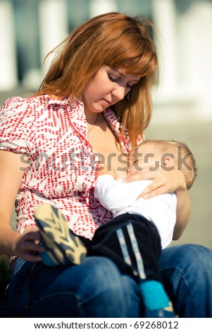 young mother feeding her baby - stock photo
