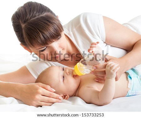young mother feeding her baby from bottle - stock photo