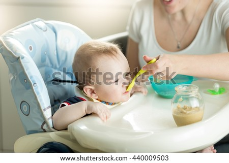 Young mother feeding her 9 months old baby son sitting in child chair on kitchen - stock photo