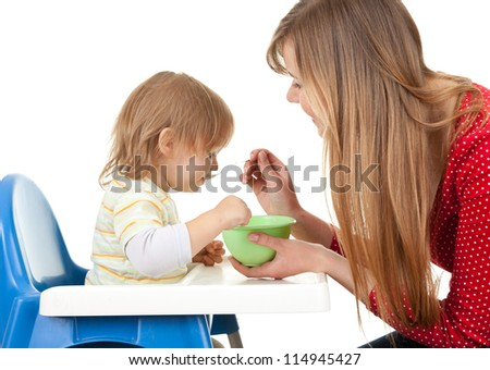 young mother feeding hungry baby in highchair, white background - stock photo