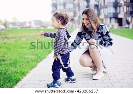 Young mother has fun with her baby boy  in the city park  - stock photo