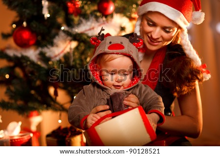 Young mother helping interested baby open present box at Christmas tree - stock photo