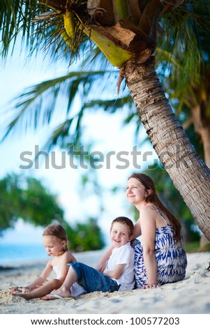 Young mother her two kids enjoying evening at beach - stock photo