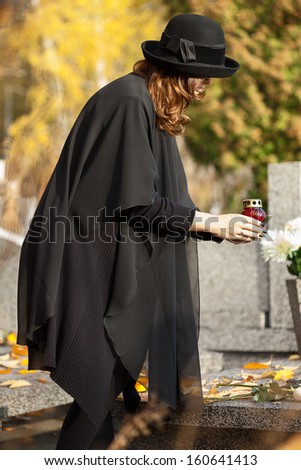 Young mother holding a red candle at graveyard - stock photo
