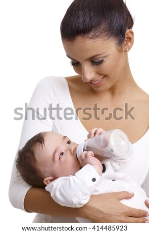 Young mother holding baby boy while baby drinking from feeding bottle, smiling. - stock photo