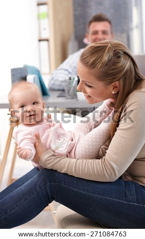 Young mother holding baby daughter on lap, playing with her, having fun. - stock photo