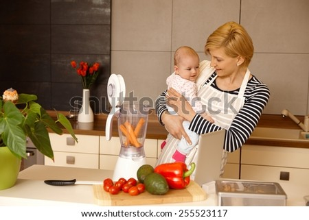 Young mother holding baby in arms, preparing baby food in the kitchen. - stock photo