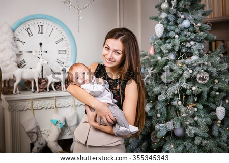 Young mother holding baby son and smiling - stock photo