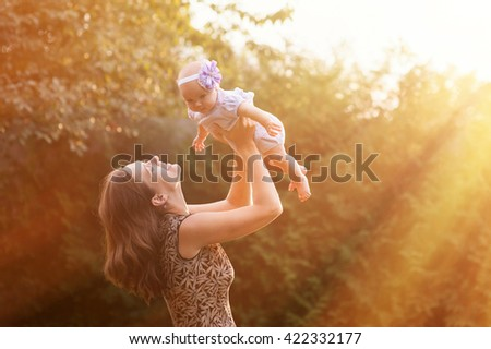 young mother holding daughter in her arms - stock photo