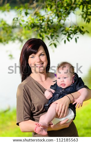 Young mother holding her baby daughter in an outdoor park by a river. - stock photo
