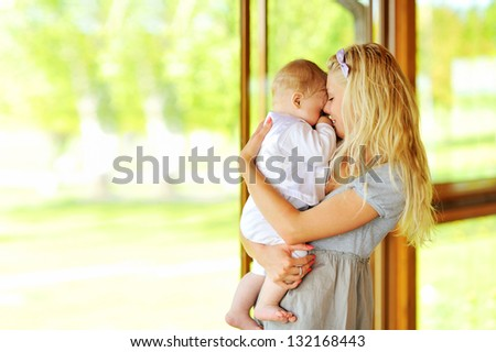 Young mother holding her little baby outdoors - stock photo
