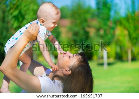 Young mother holding her little son at park - stock photo