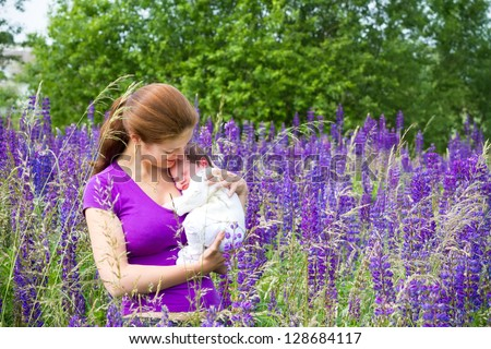 Young mother holding her newborn baby in a purple flower field - stock photo