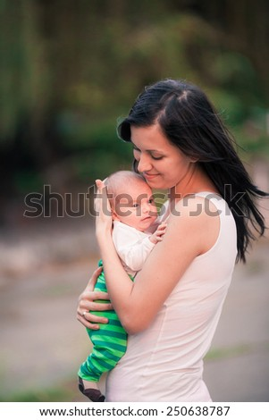 Young mother holding her newborn baby outdoor - stock photo