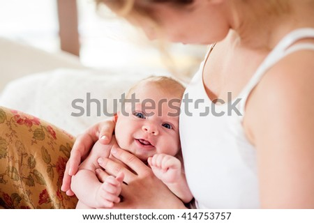 Young mother holding her newborn baby son, home bedroom - stock photo