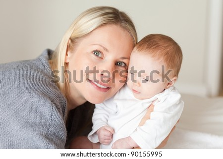 Young mother holding her newborn close - stock photo