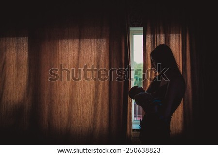Young mother holding newborn baby near window - stock photo