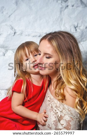 Young mother hugging her daughter, closeup portrait shot in the studio. The concept of family happiness. - stock photo