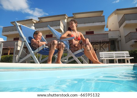 young mother in orange pareo and son sitting on beach chair near pool and smiling, house - stock photo