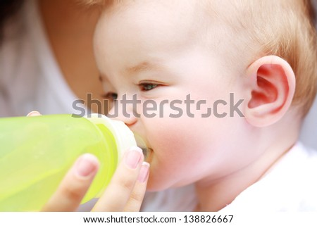 Young mother is feeding her baby from a bottle outdoor - stock photo