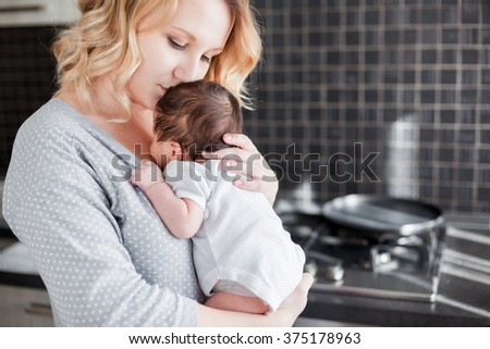 Young mother is holding her newborn baby - stock photo