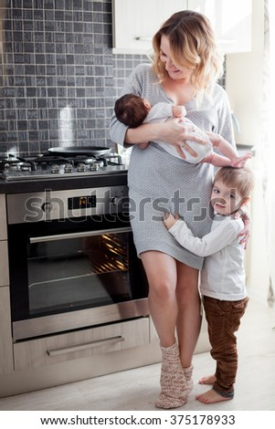 Young mother is holding her newborn baby and toddler at the kitchen - stock photo