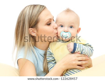 Young mother kisses and hugging baby - stock photo
