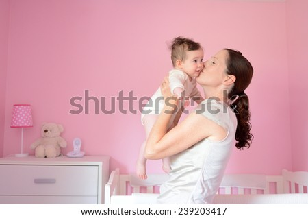 Young mother kisses her baby (girl age 06 months). Concept photo parenthood and motherhood. - stock photo