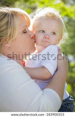 Young Mother Kissing and Holding Her Adorable Baby Boy in the Park. - stock photo