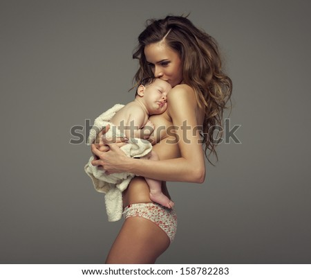 Young mother kissing baby - stock photo