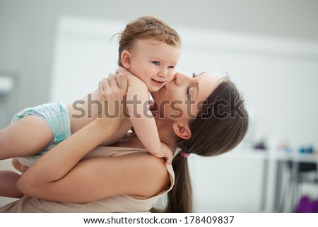 Young mother kissing her adorable baby boy. - stock photo