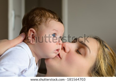 Young mother kissing her adorable baby boy in a room - stock photo