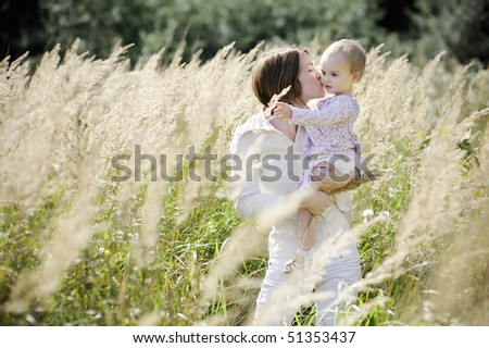 Young mother kissing her toddler girl in the fields - stock photo