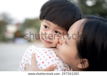 Young mother kissing son outdoors - stock photo