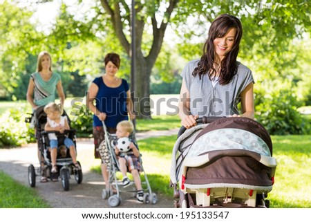 Young mother looking at baby in stroller at park with friends and children in background - stock photo