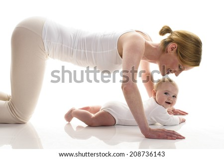 Young mother makes with her 6 month old daughter postnatal exercises, isolated against white background. She kneels on the ground and makes about the baby pushups. - stock photo