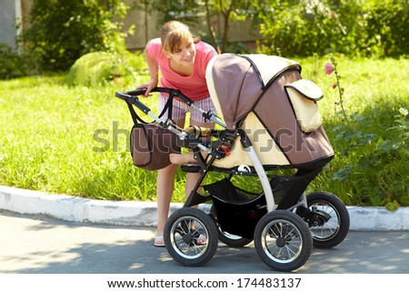 young mother on a walk in the park with a baby in a stroller - stock photo