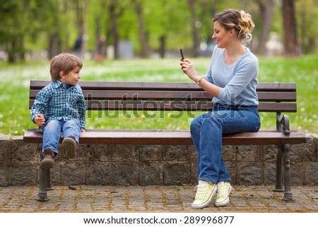 Young mother photographing her cute little son sitting on a park bench - stock photo