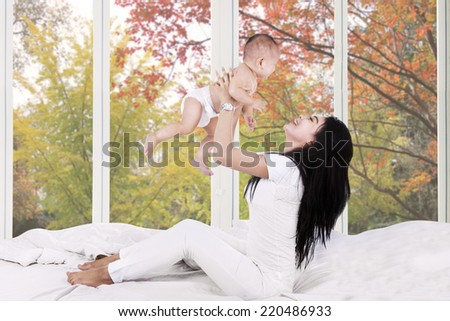 Young mother playing on bed with her baby at home in autumn - stock photo