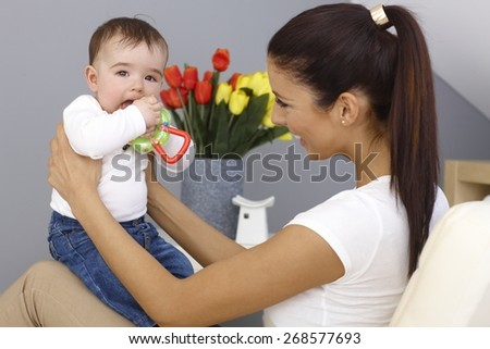 Young mother playing with baby boy, holding him on lap, smiling happy. Baby holding toy. - stock photo